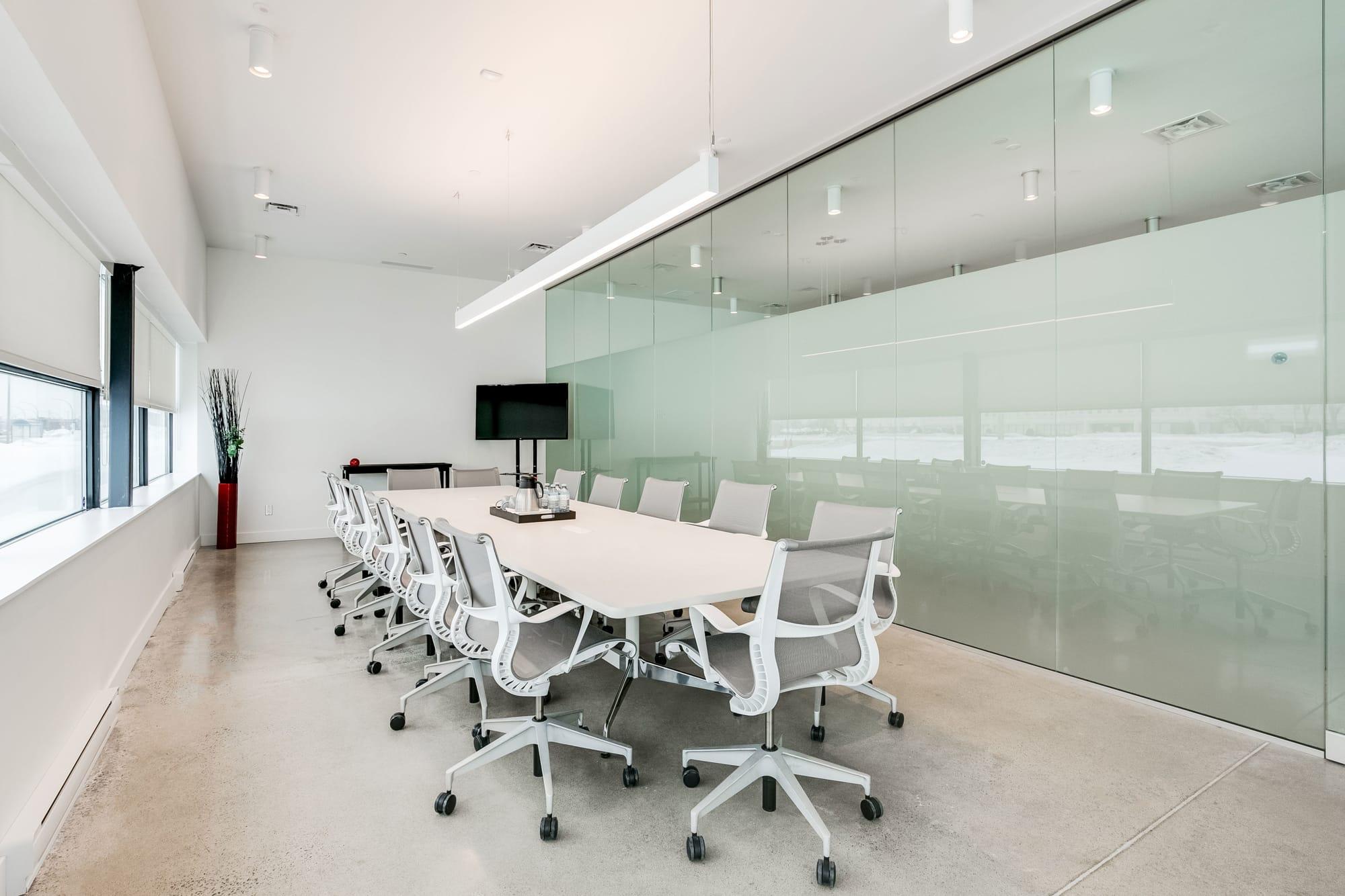salle de conférence dans un bureau rénové avec table et chaises blanches