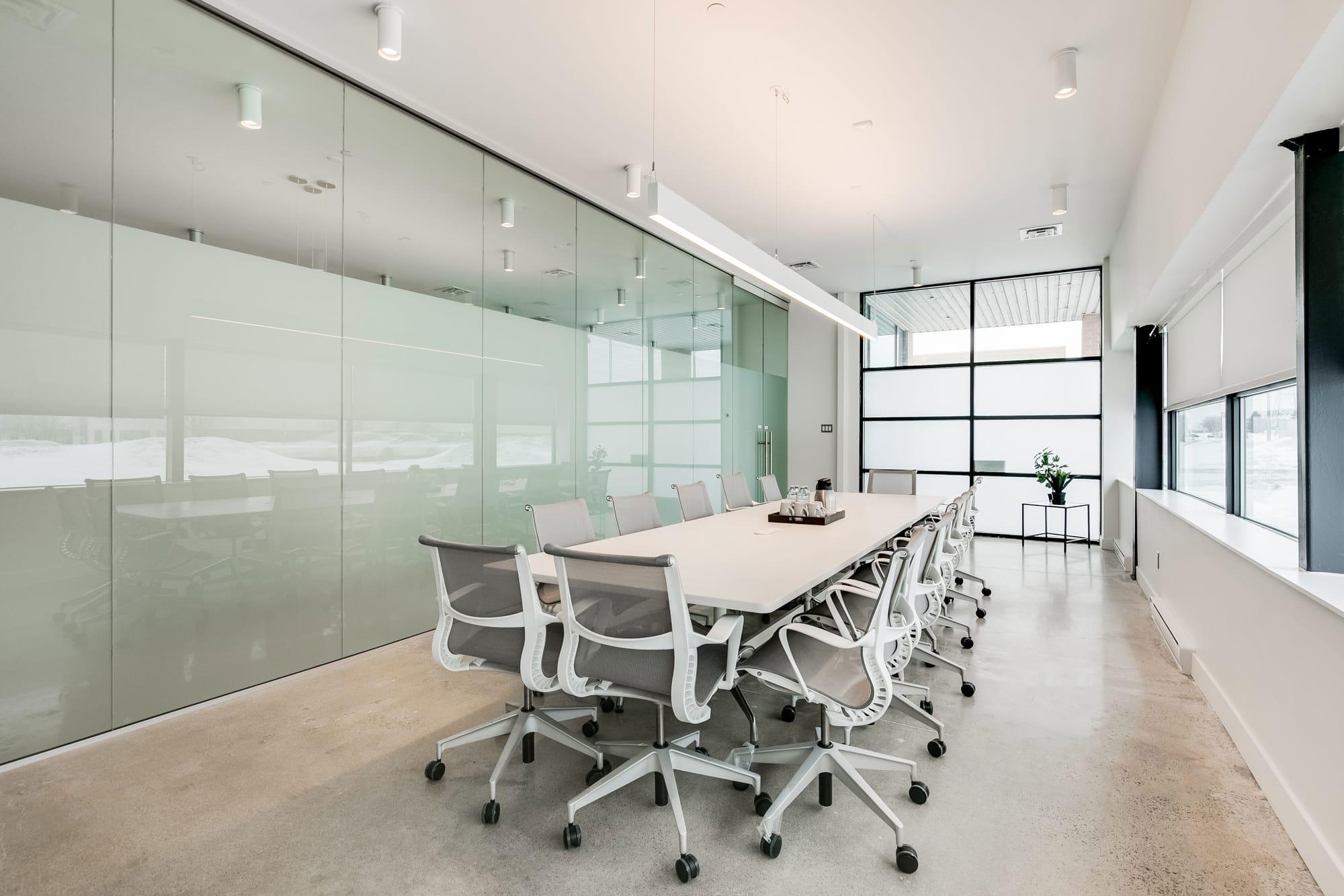 design de salle de réunion avec table et chaises blanches + mur vitré
