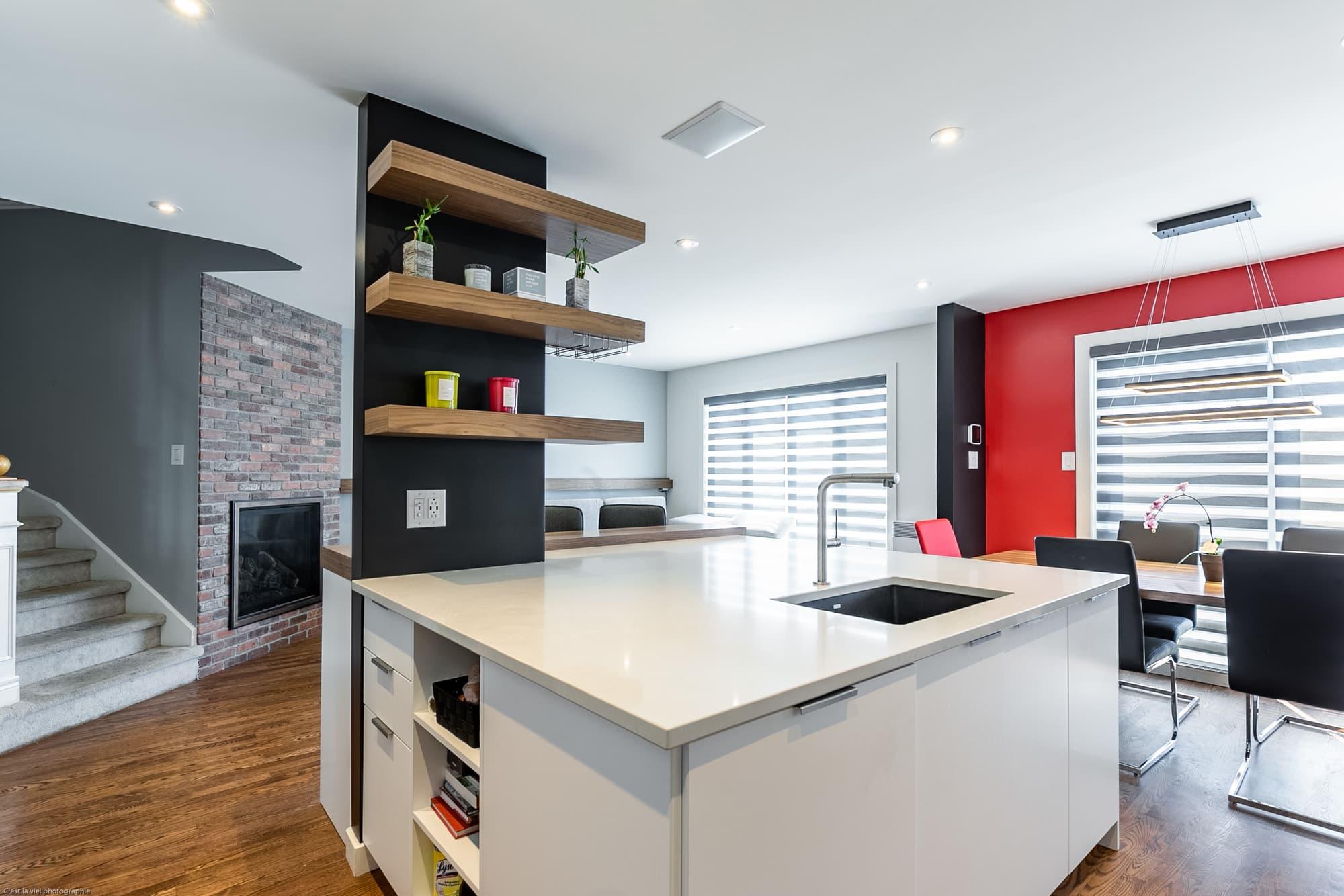 grand îlot de cuisine blanc dans une cuisine ouverte sur salon et salle à manger