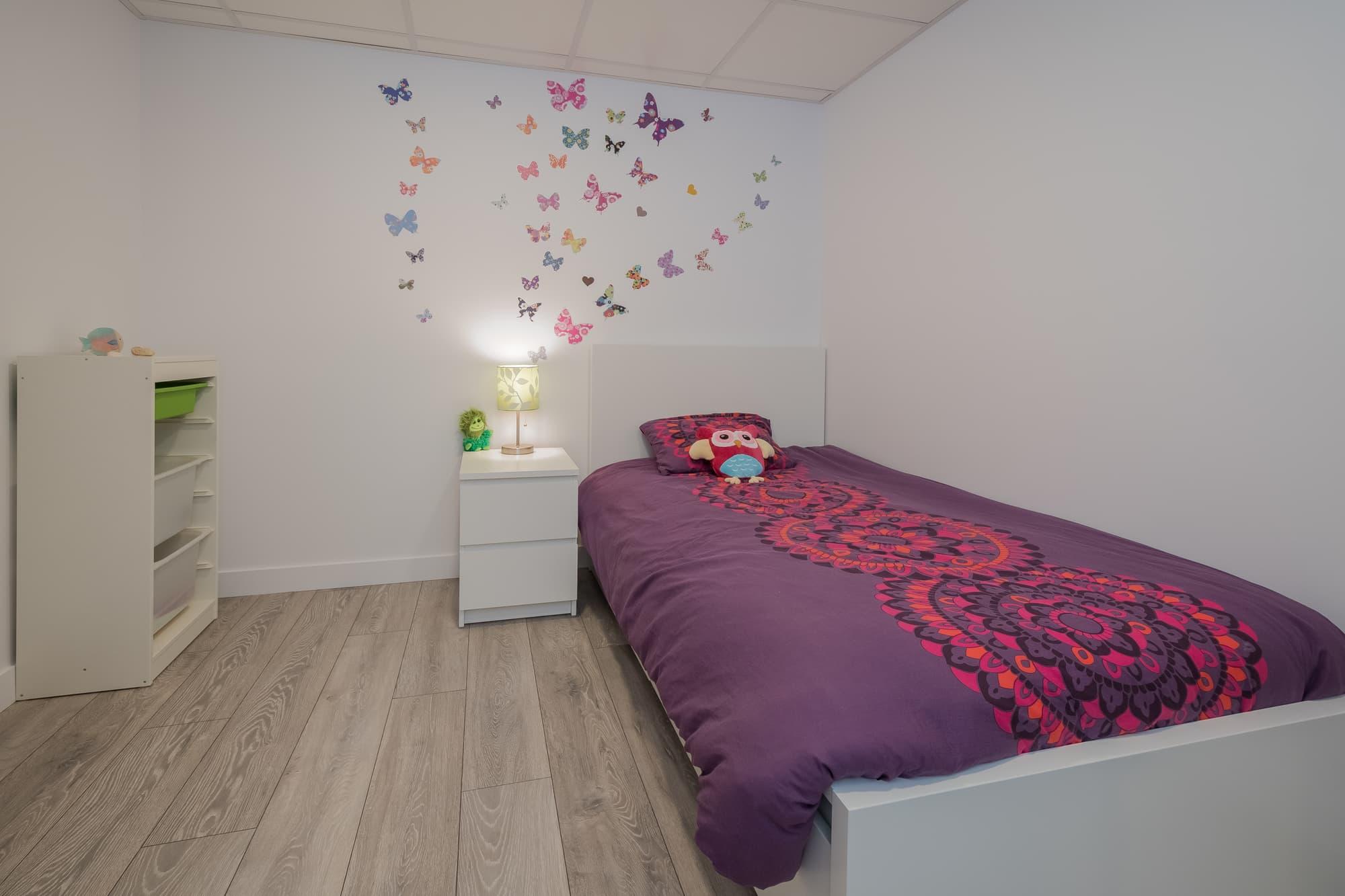 chambre d'enfant (fillette) avec couvre-lit mauve et papillons sur le mur dans un sous-sol nouvellement rénové