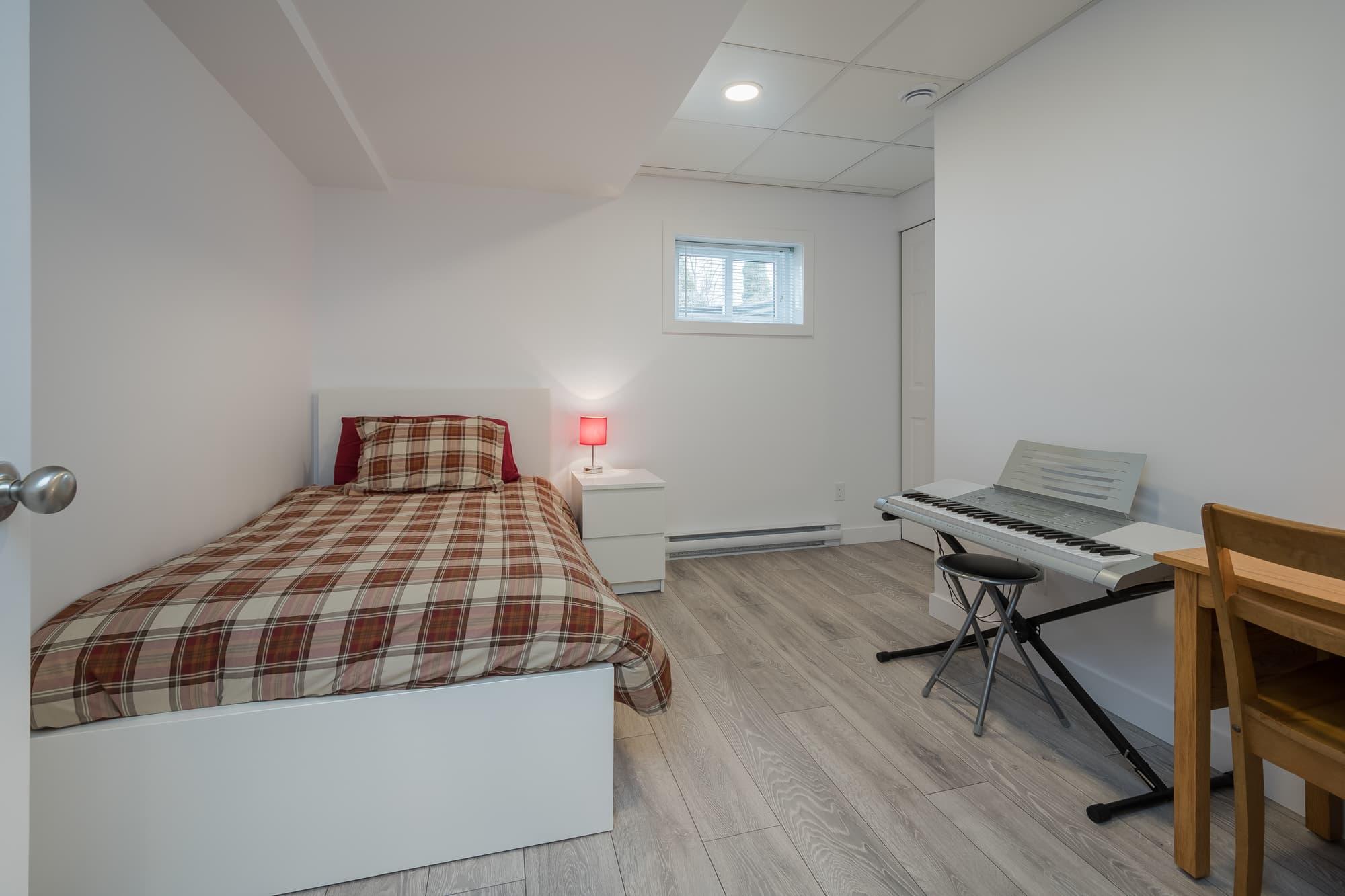chambre dans un sous-sol rénové avec couvre-lit carreauté et plancher flottant pâle