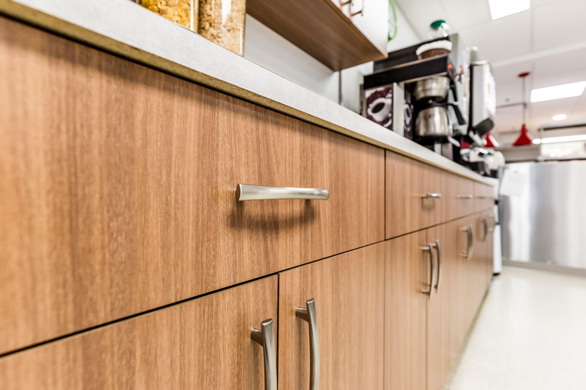 rénovation cuisine commerciale avec armoires en bois brun pâle et poignées argent