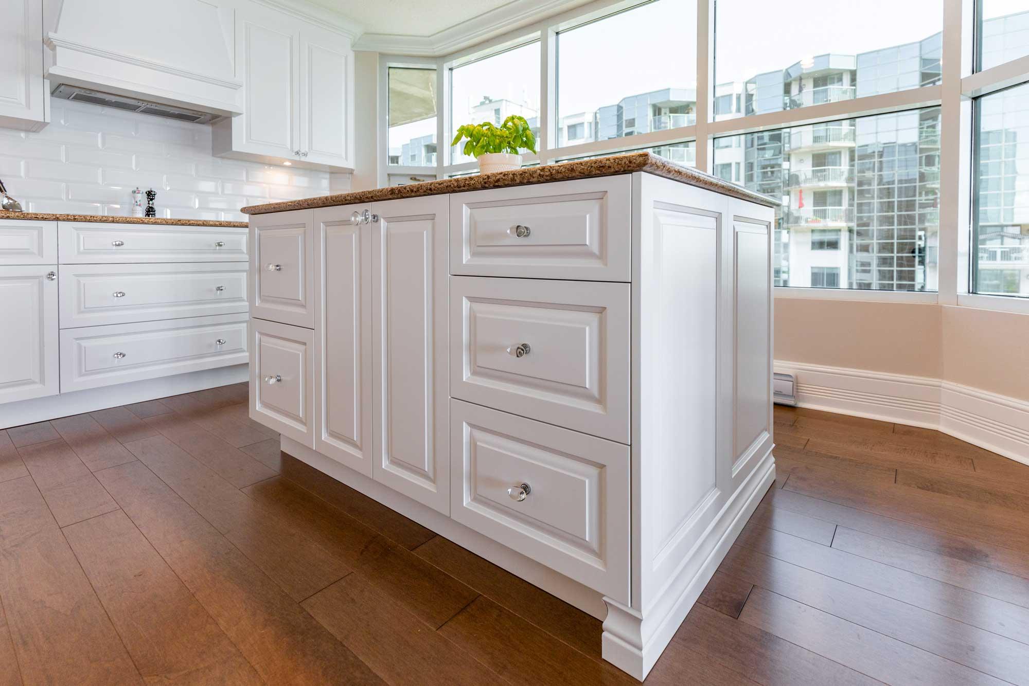 îlot de cuisine blanc avec comptoir en granite beige et plancher en bois franc