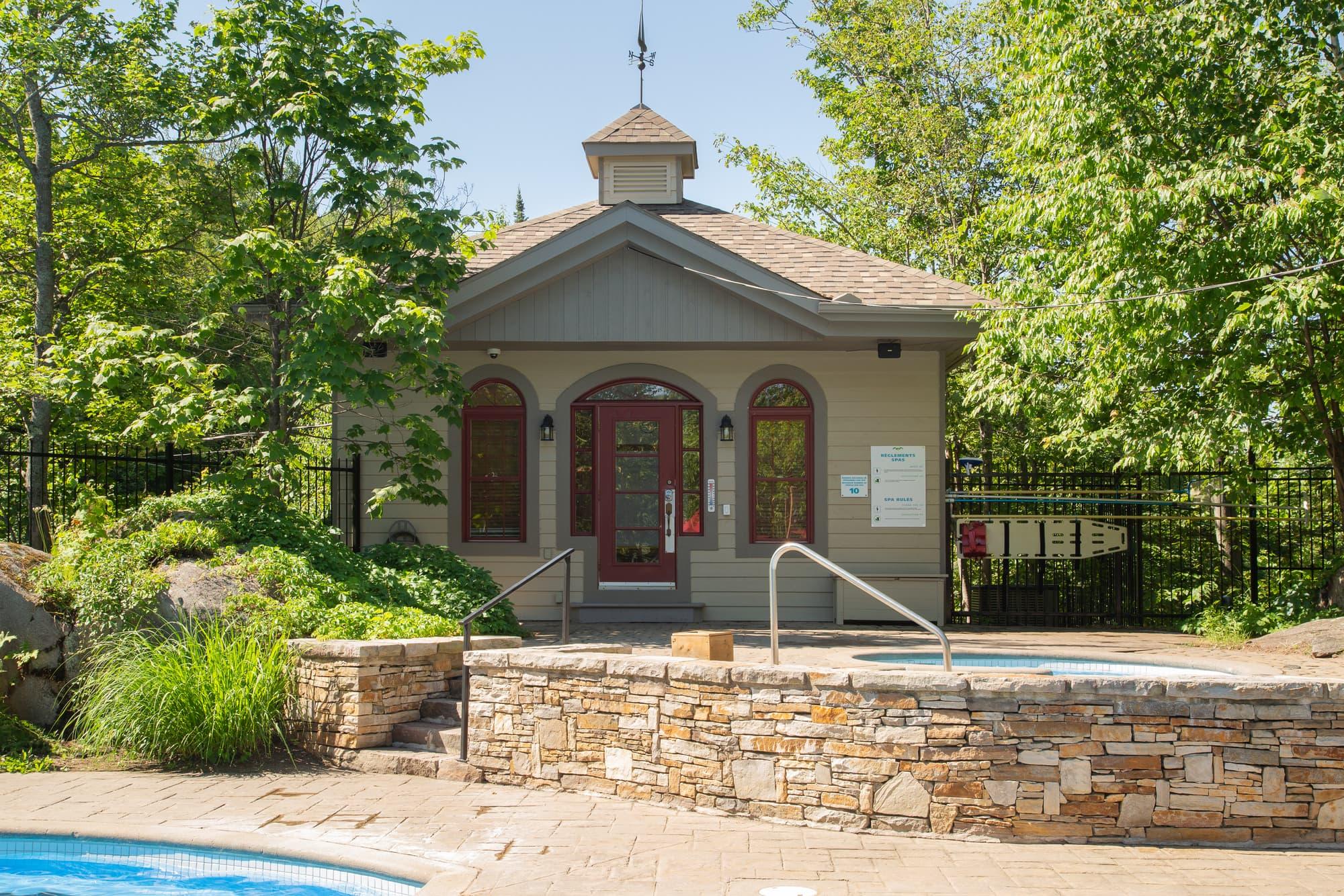 petit pavillon de couleur argile où se trouve la piscine extérieure d'une association de copriétés à Mont-Tremblant