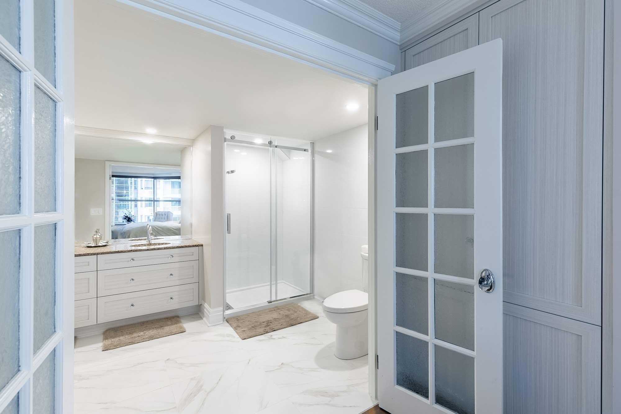 rénovation de salle de bain avec vanité blanche et douche vitrée