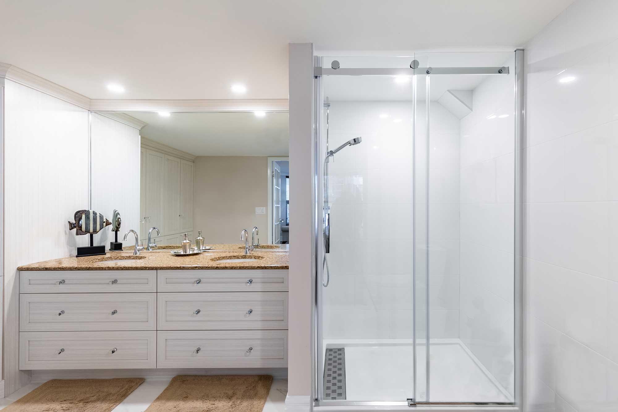 salle de bain rénovée avec vanité suspendue blanche et douche vitrée