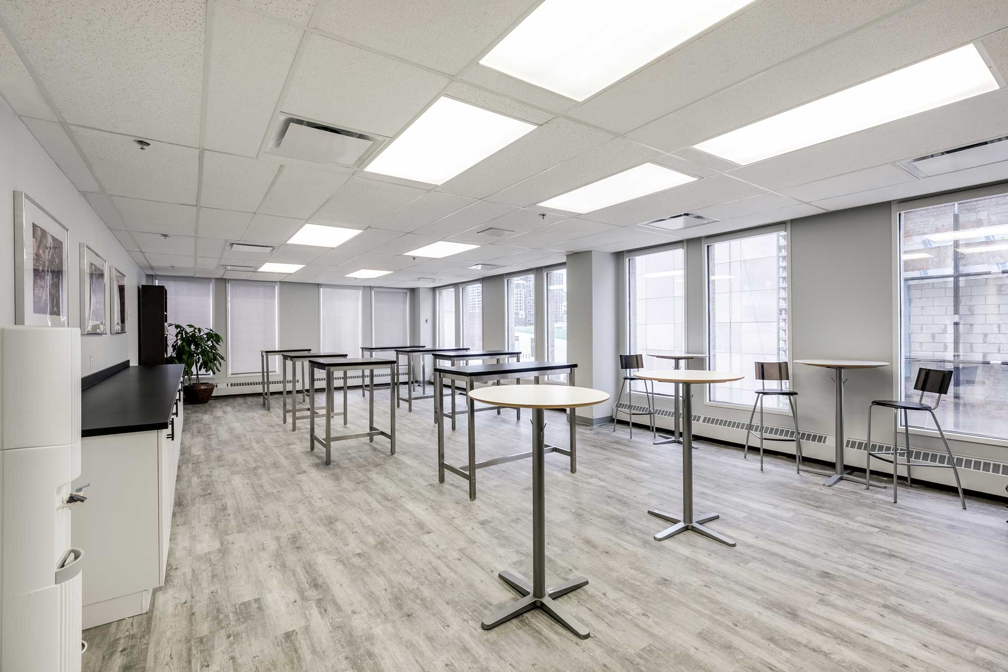 cafétéria dans une entreprise avec tables hautes et plancher en vinyle gris imitation de bois