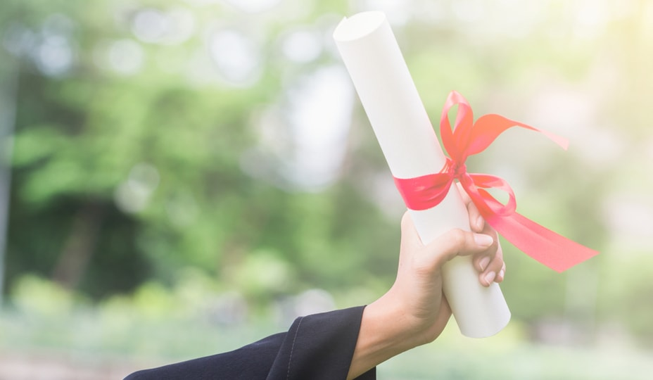 graduate student holding his diploma in his hand