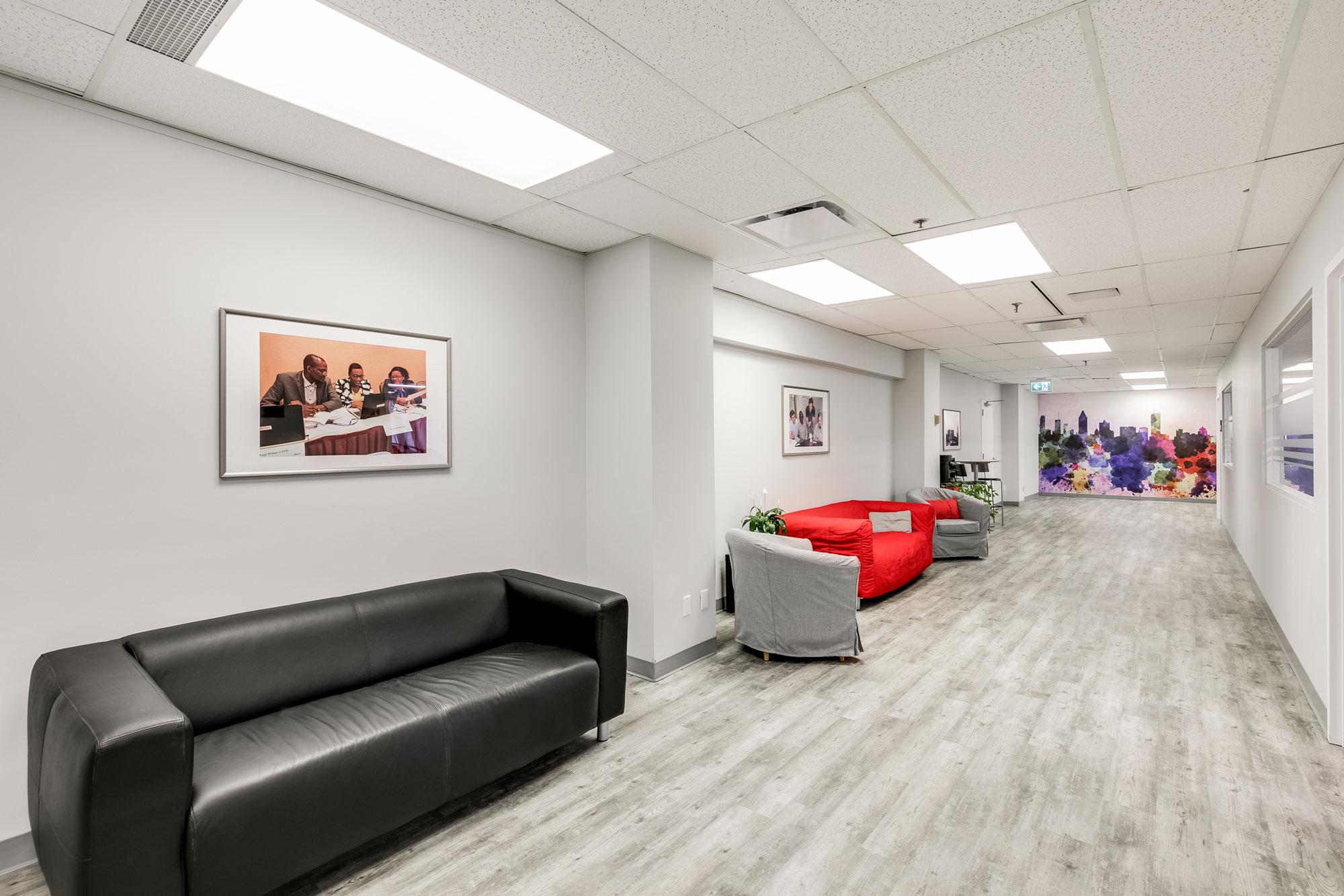 espace détente dans une entreprise avec divan en cuir noir et autres fauteuils + plancher en vinyle gris