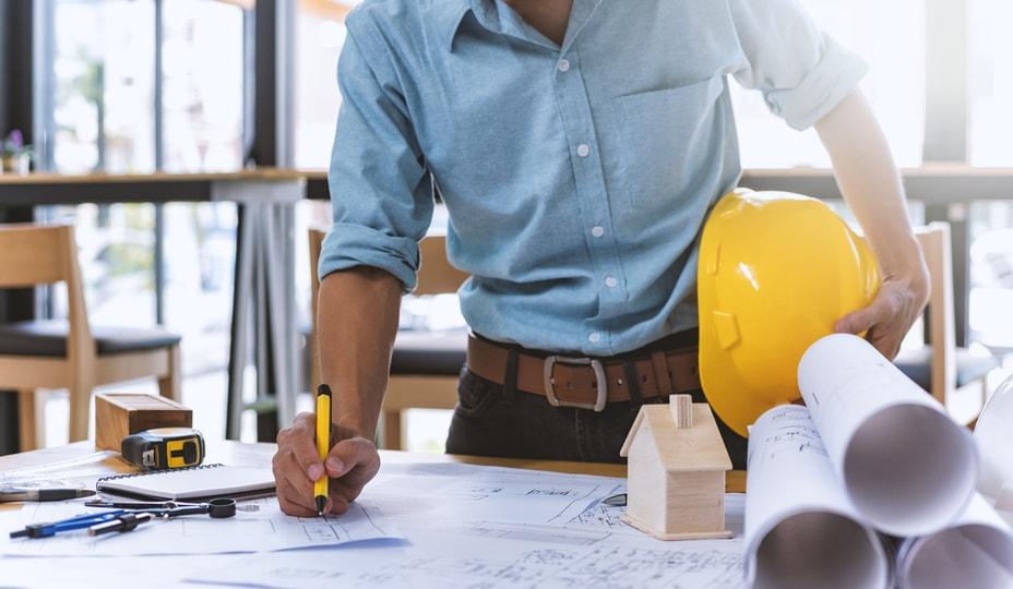 entrepreneur général avec chemise bleue et casque jaune sous le bras travaillant sur plans
