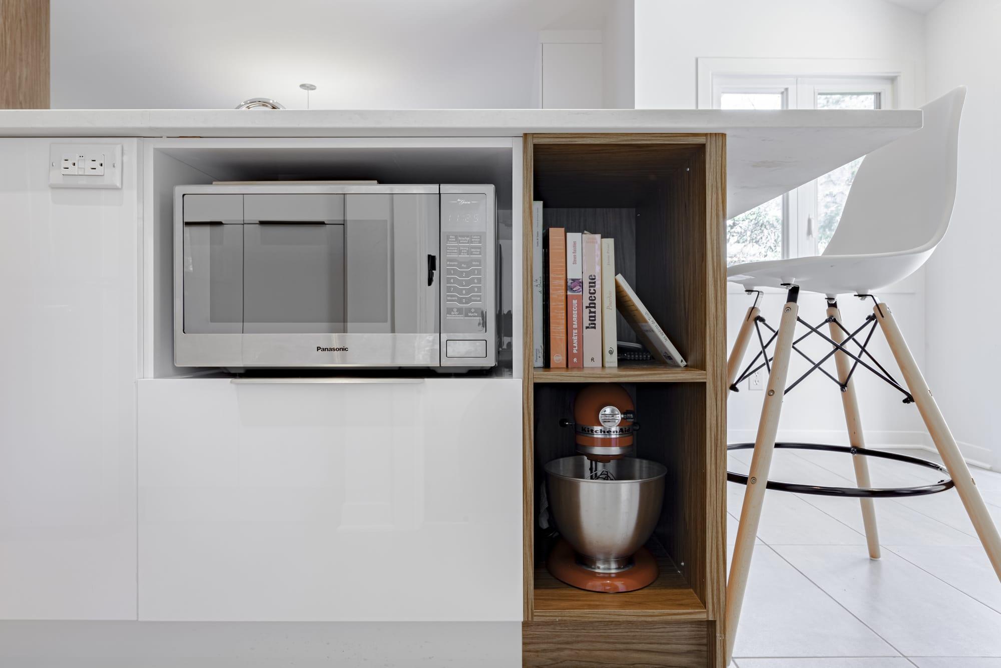 rangement dans une cuisine rénovée avec espace pour micro-ondes et livres