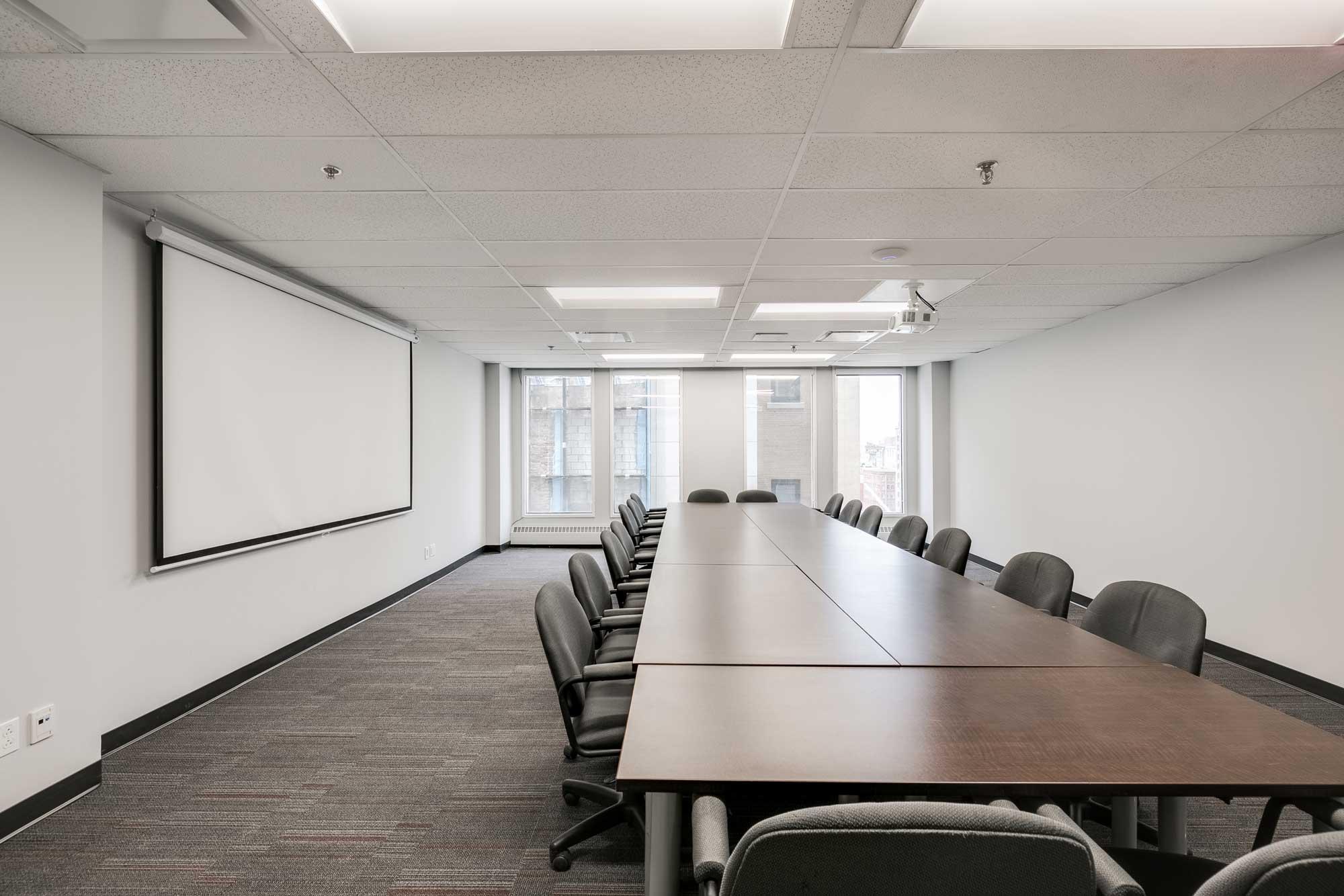 salle de conférence avec murs blancs et écran pour projecteur