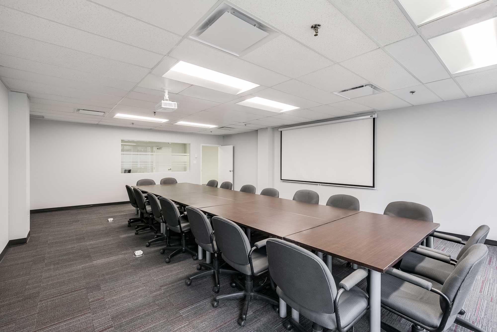 salle de réunion avec écran pour projecteur et mur blancs