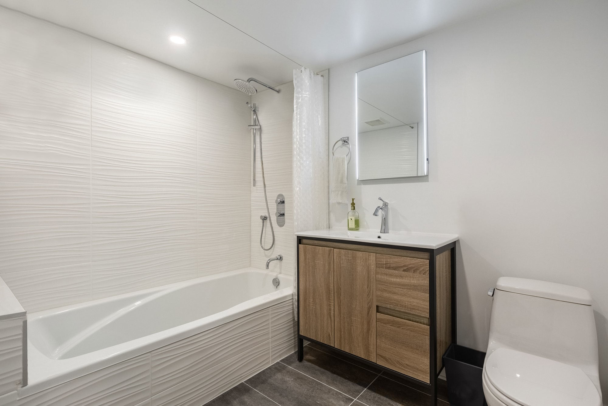 modern basement bathroom with wooden vanity, bath and toilet