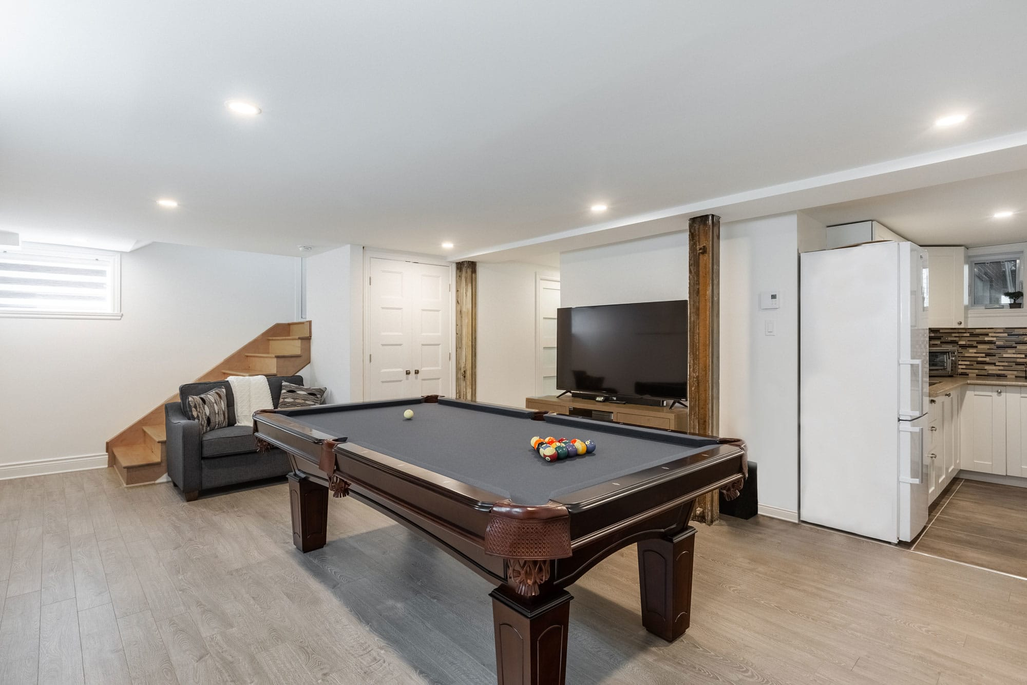 basement finishing with pool table and television