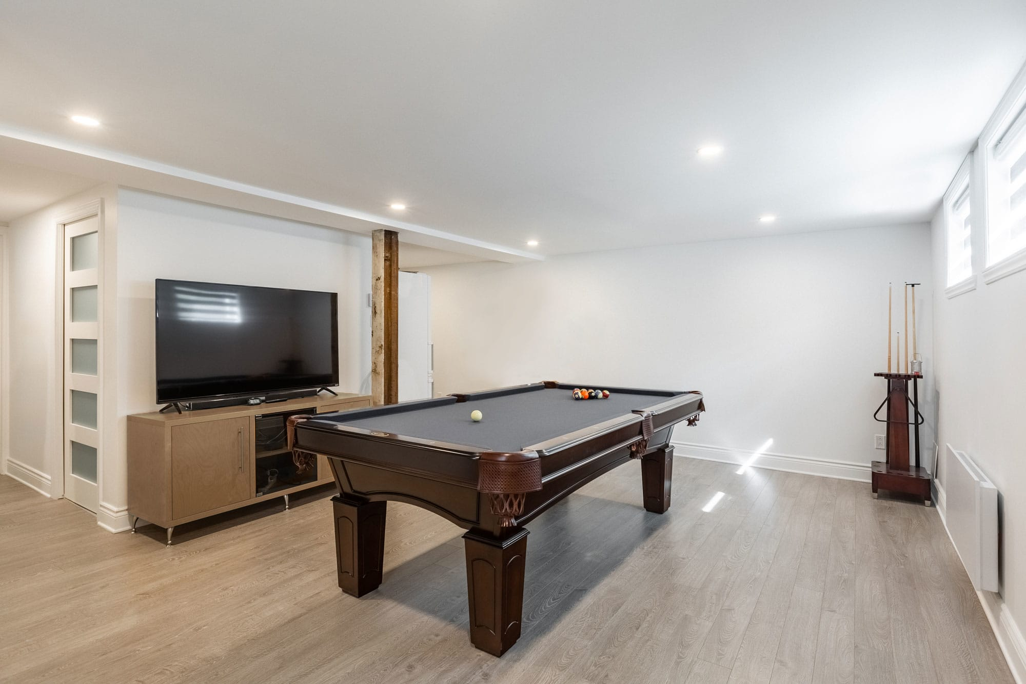 modern basement renovation with pool table and television