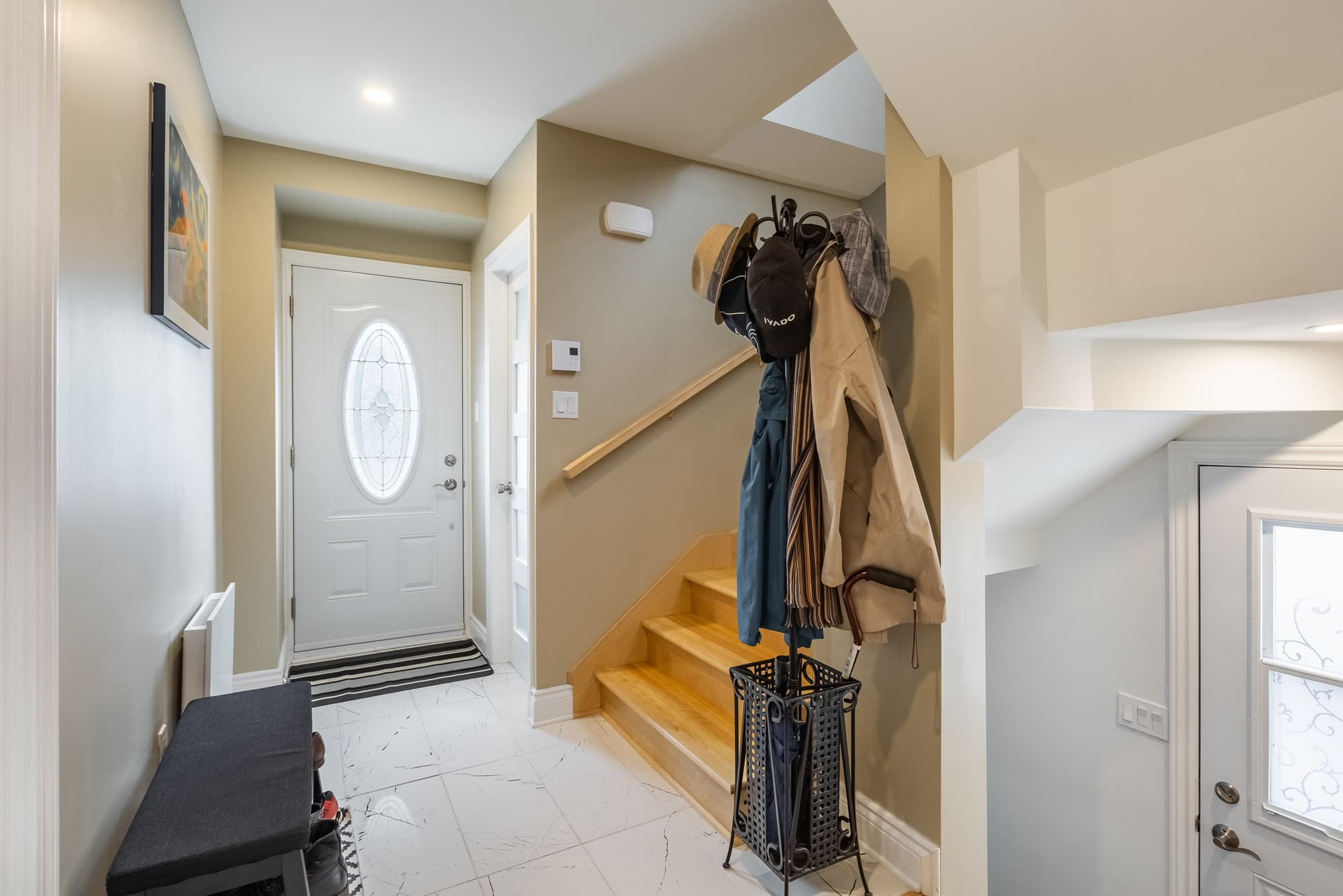 entryway with white door and coat hanger