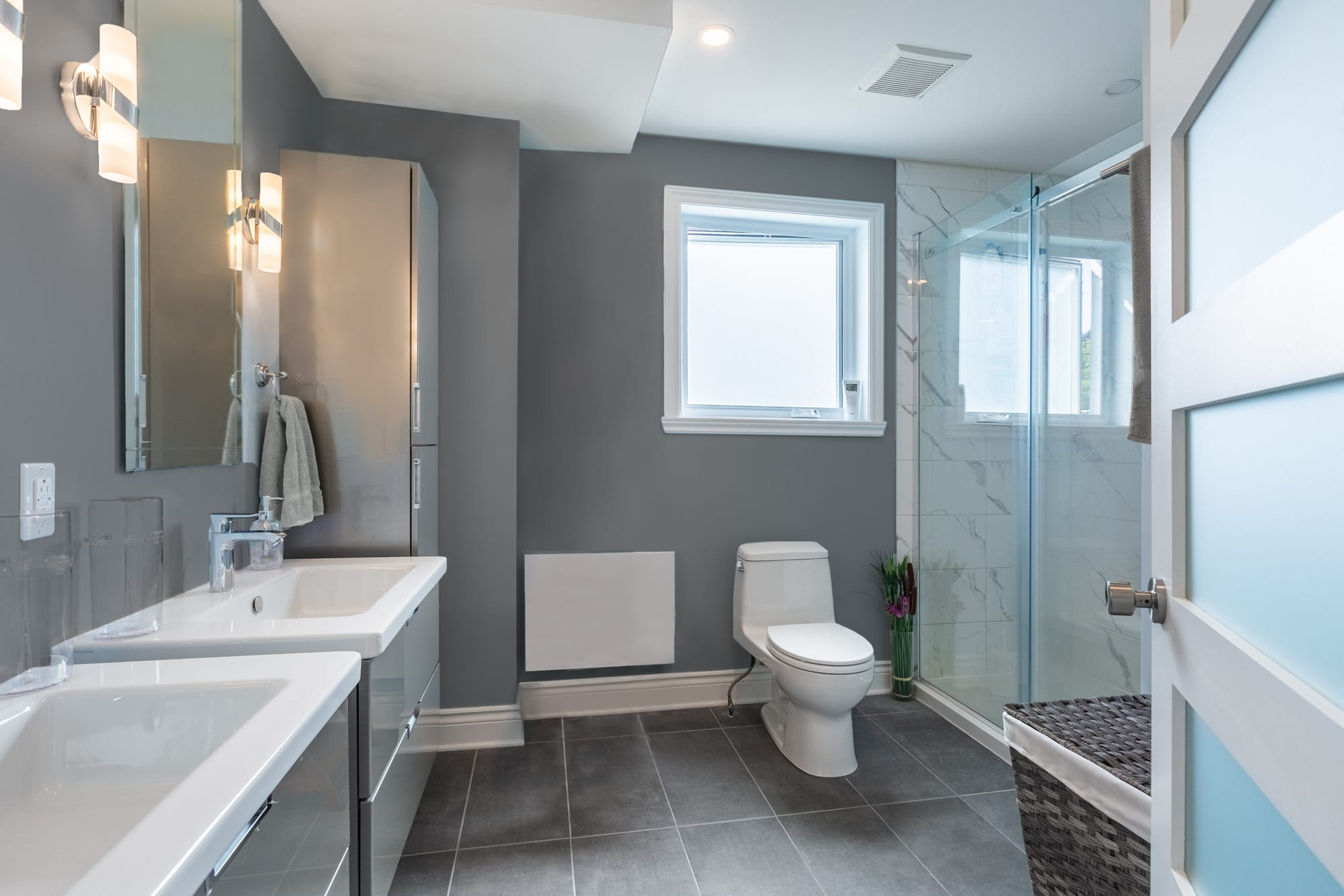 modern grey bathroom with 2 suspended vanities and glass shower