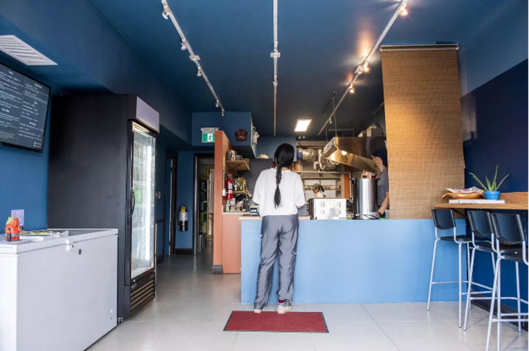 rénovation d'un restaurant avec cliente debout devant comptoir bleu