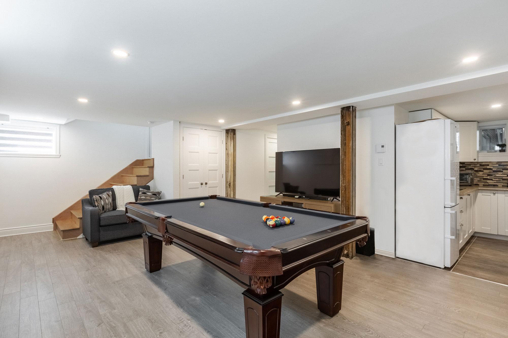 aménagement de sous-sol avec table de billard et téléviseur