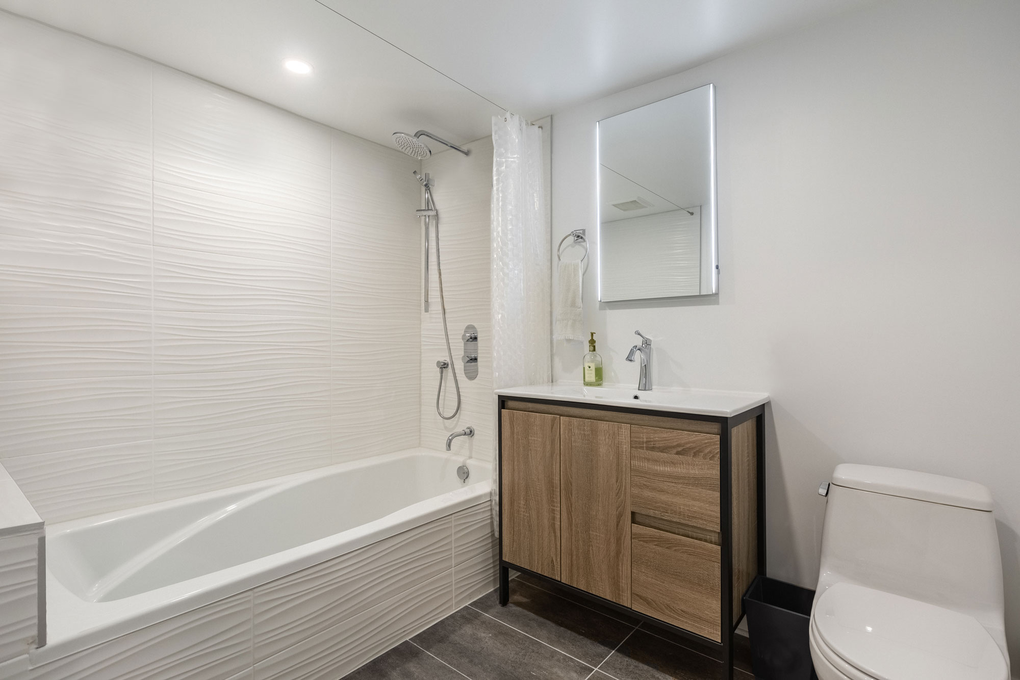 basement bathroom with shower-bath and wooden vanity