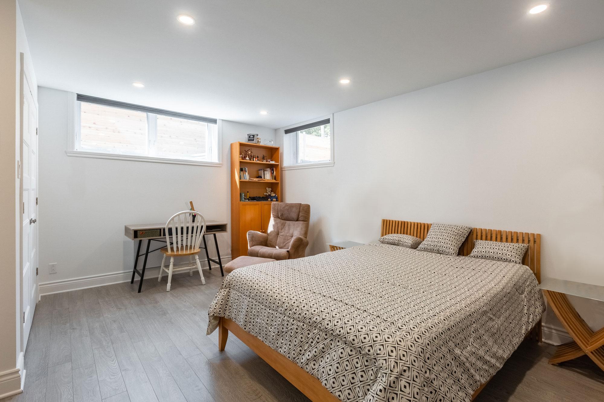 basement bedroom with floating floor, bed and wooden shelf