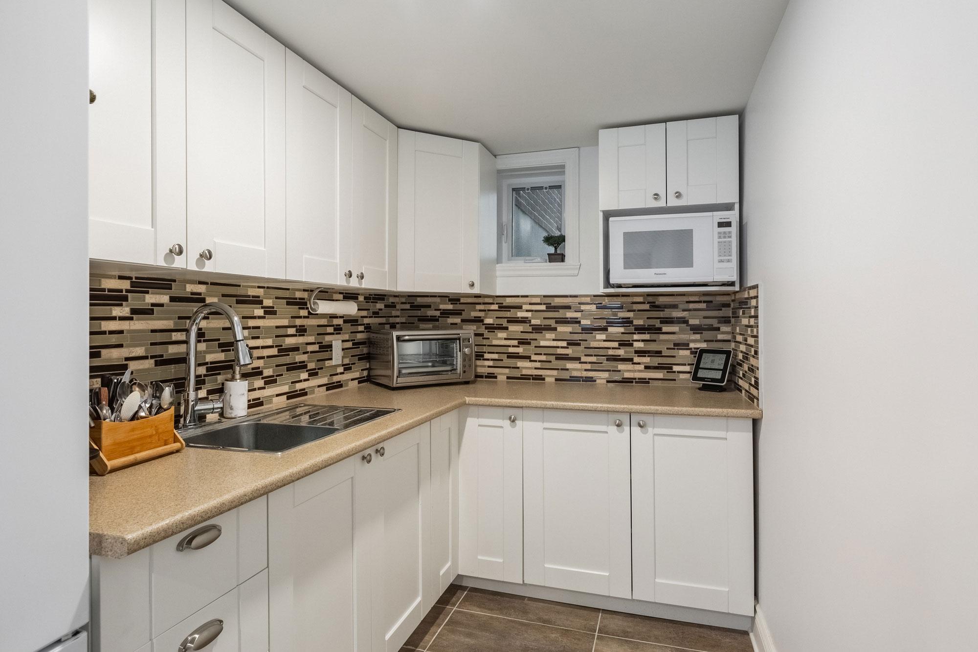 basement kitchen with white cabinets and ceramic backsplash