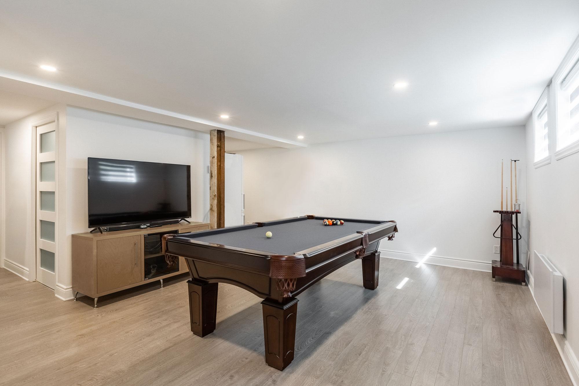 rénovation de sous-sol avec table de billard et téléviseur