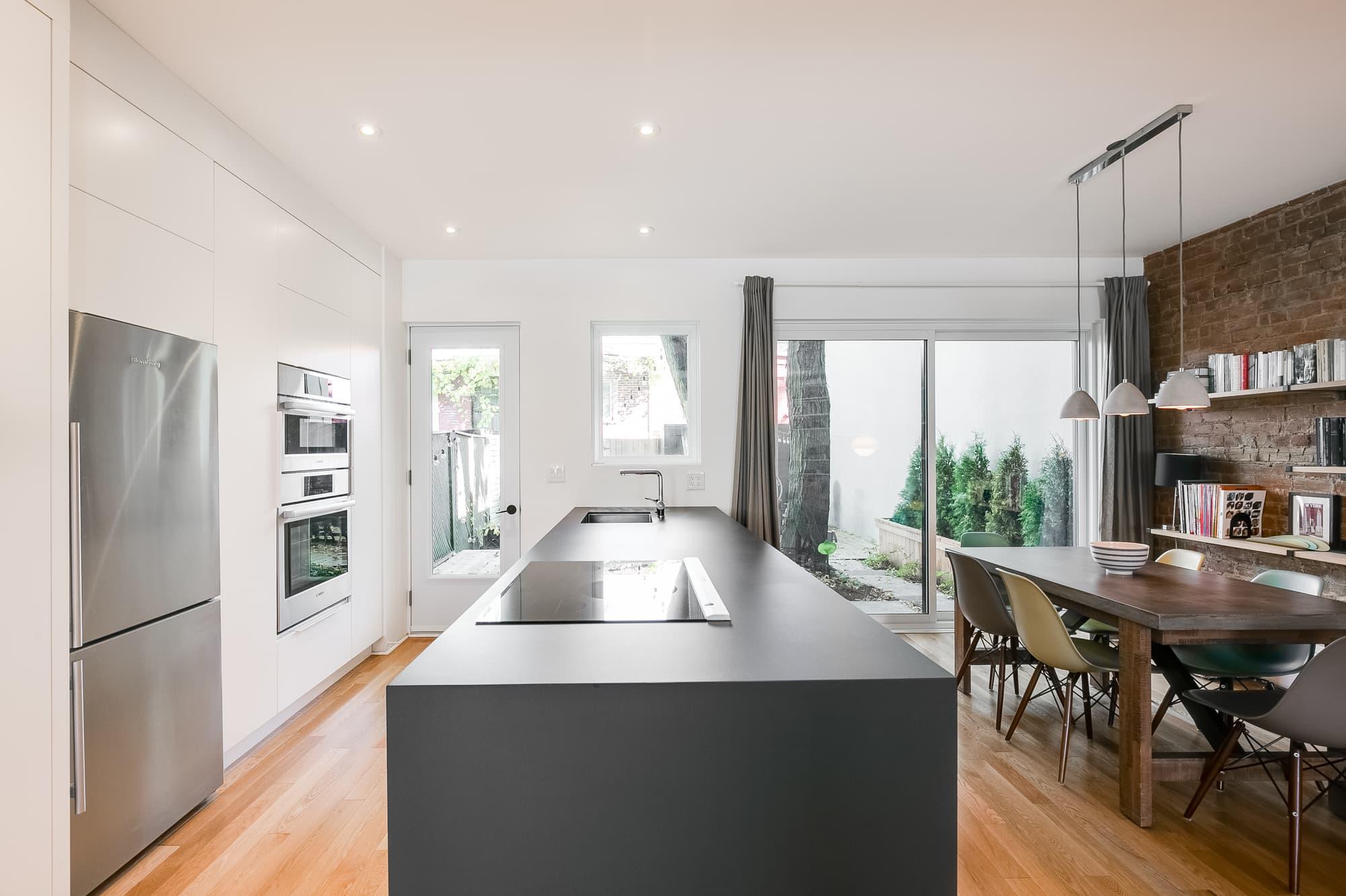 cuisine rénovée moderne blanche avec grand îlot et mur de brique dans la salle à manger