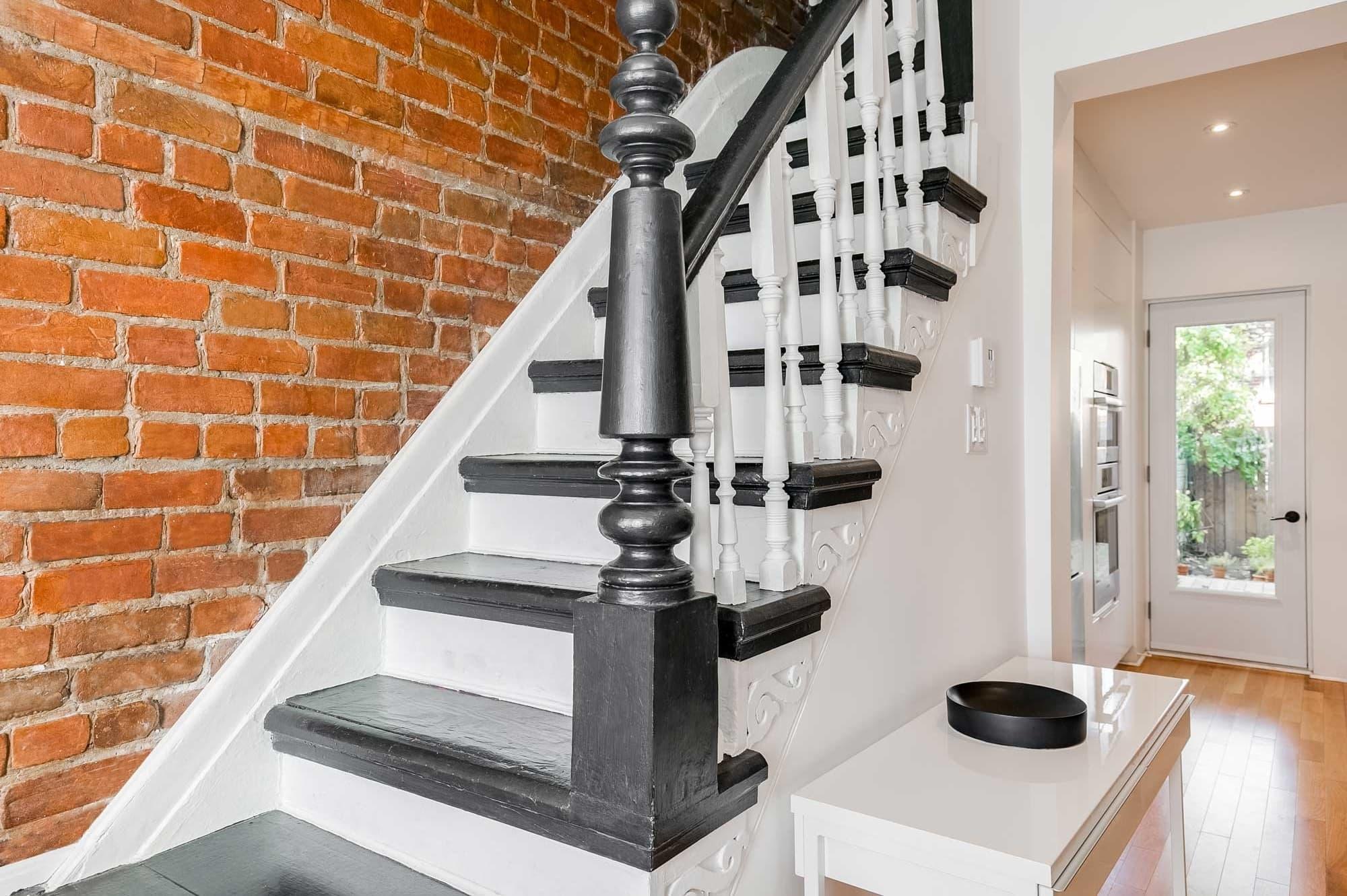 escalier intérieur en bois avec marches, rampes et poutres noires + contre-marches blanches et mur en brique