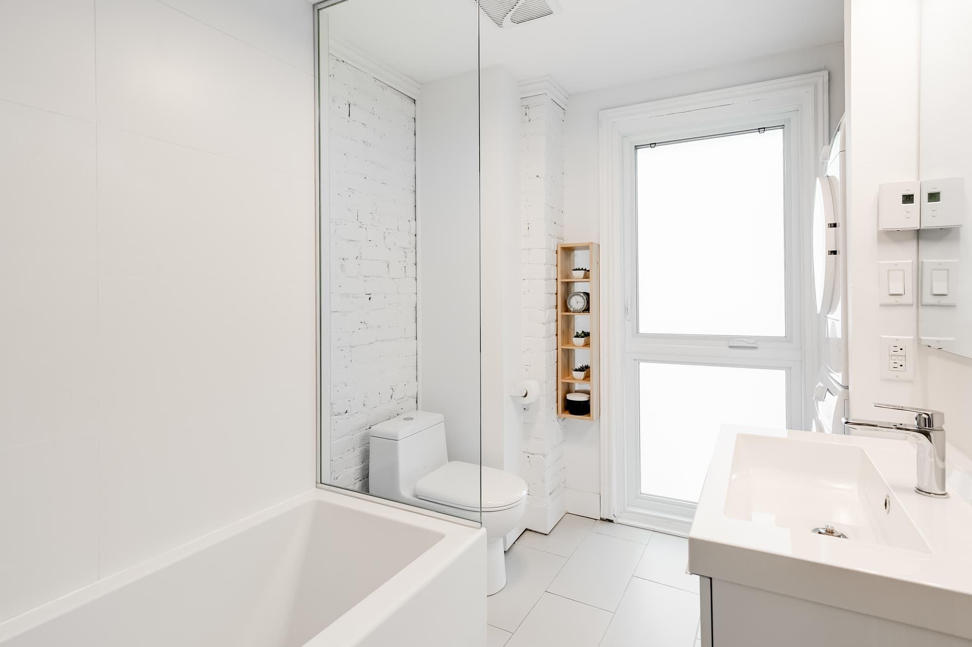 rénovation de salle de bain blanche avec mur en brique blanc