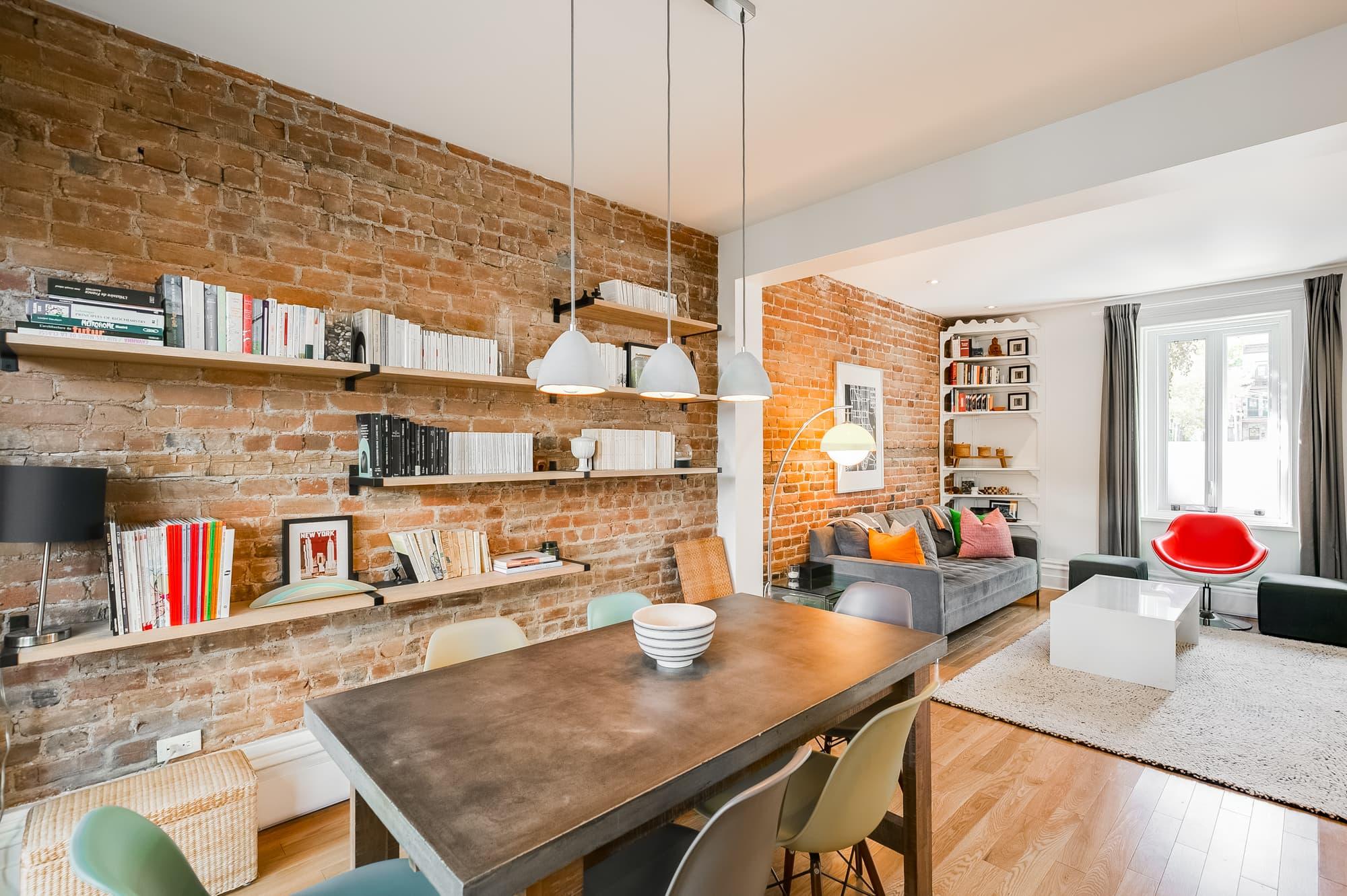 salle à manger avec mur en brique et tablettes