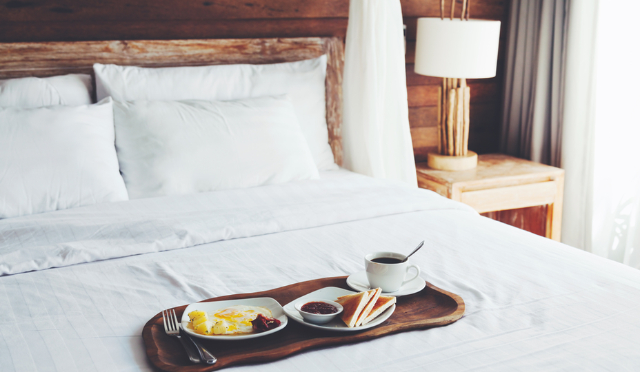 tray of breakfast food on white bedding
