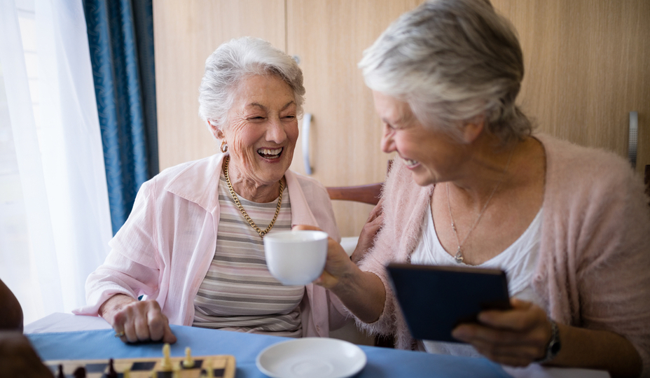 two senior women laughing while drinking coffee