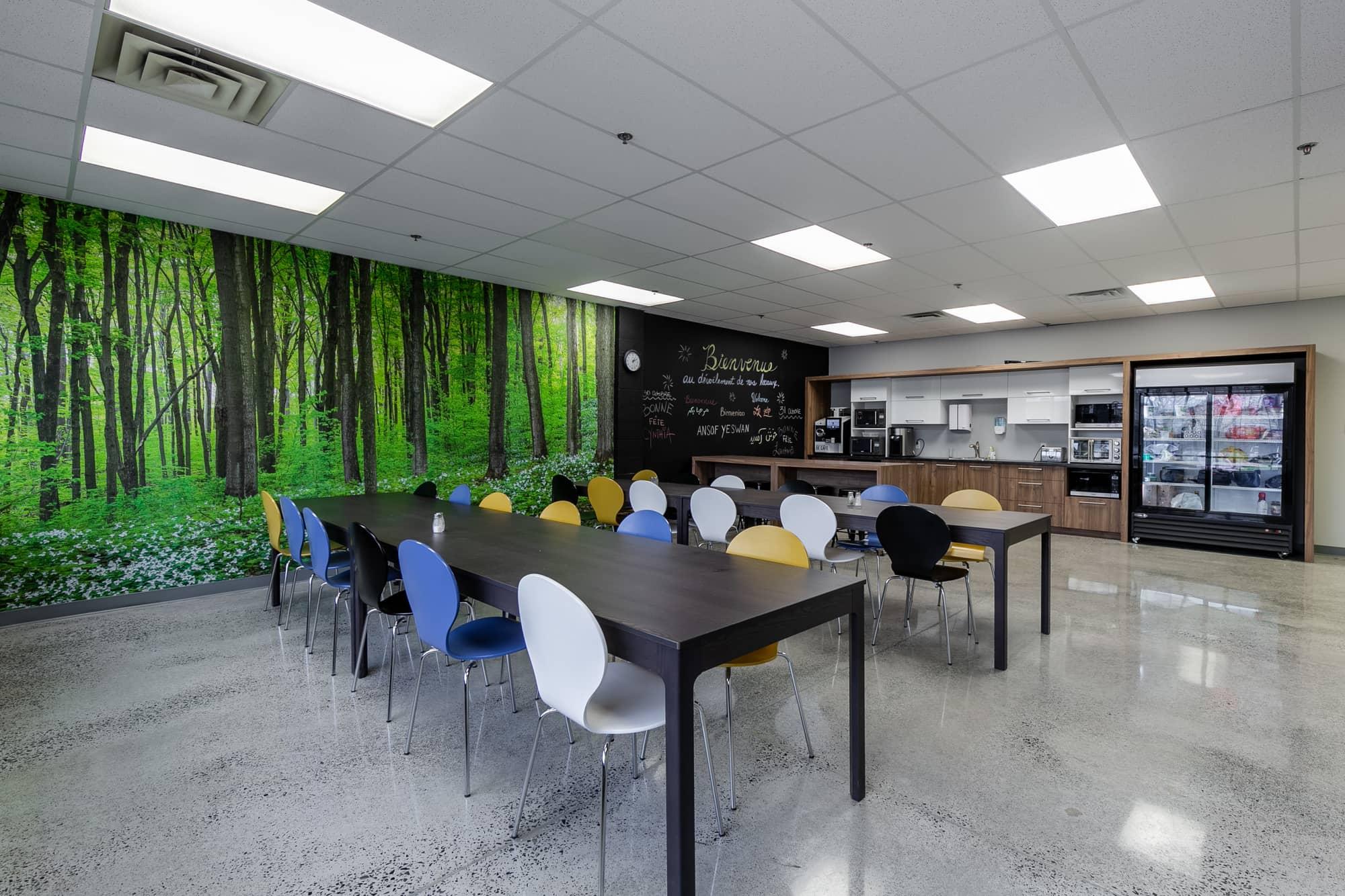 cafétéria d'entreprise avec murale colorée et différentes tables et chaises