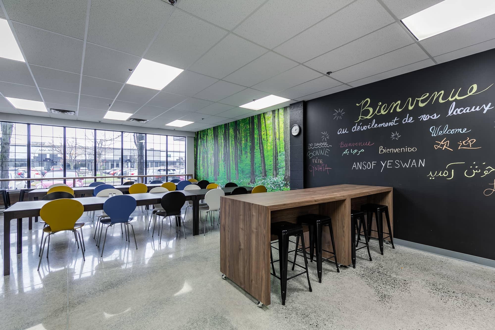 salle de pause entreprise avec comptoir, bancs, tables et tableau noir