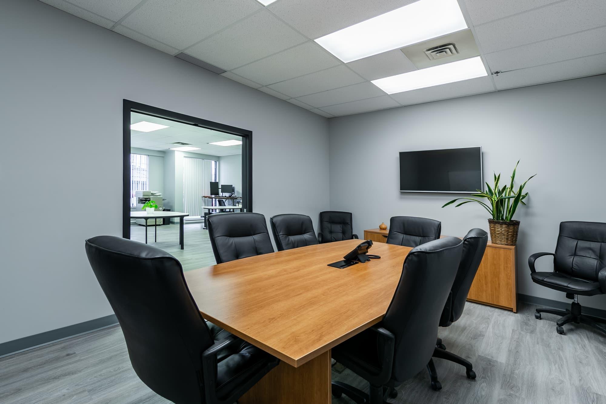 salle de réunion avec table en bois et chaises en cuir