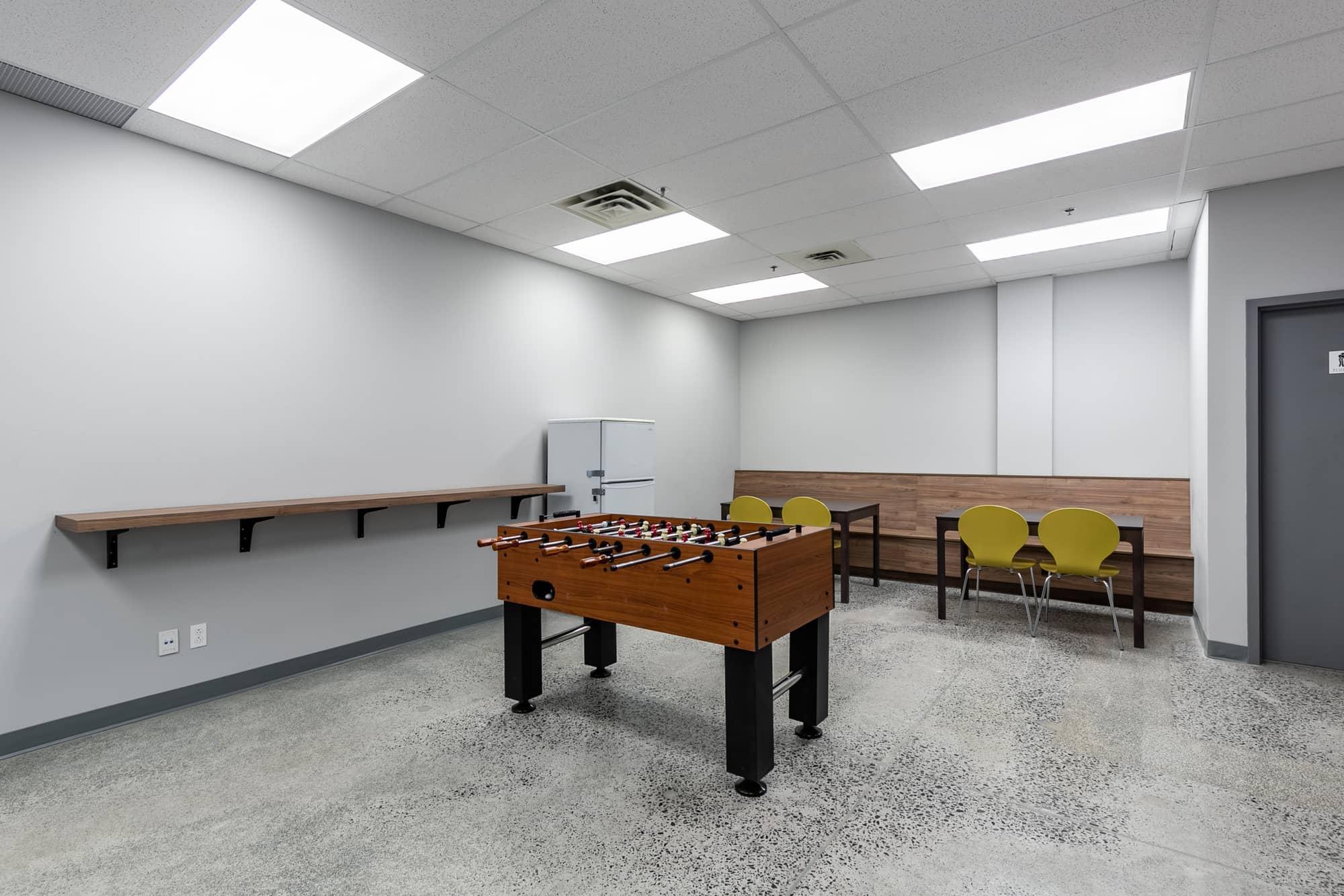 salle de repos dans une entreprise nouvellement rénovée avec table de baby foot, réfrigérateur et tables