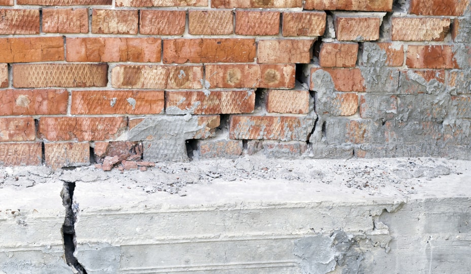 old brick wall with large cracks in it down to the foundation - building envelope problems