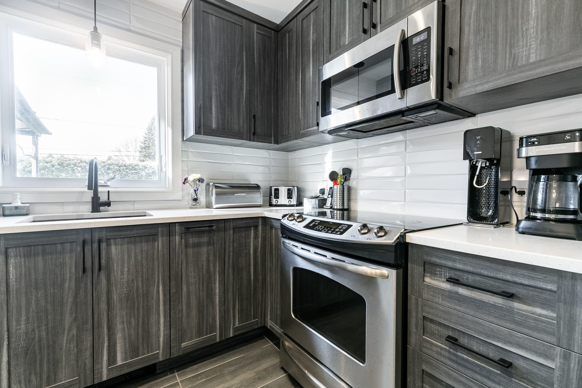 cuisine design de style comtemporain avec armoires gris foncé et dosseret en céramique blanc