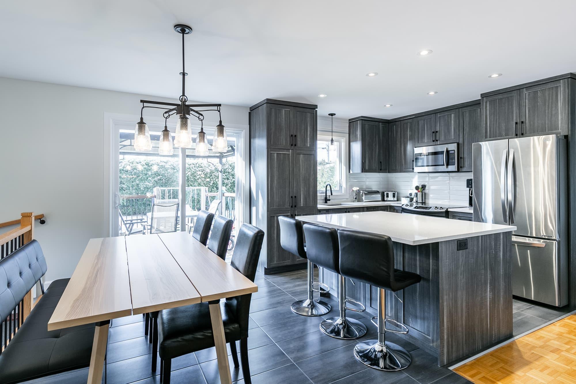 cuisine moderne avec armoire gris foncé et îlot avec coin lunch et bancs