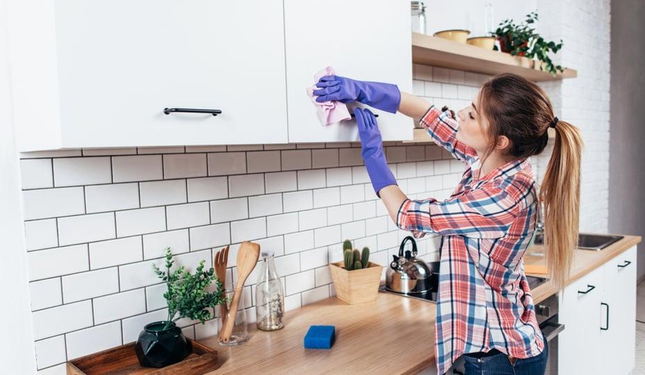 femme nettoyant armoires de cuisine blanches