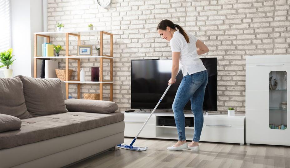 jeune femme effectuant un nettoyage de plancher de salon