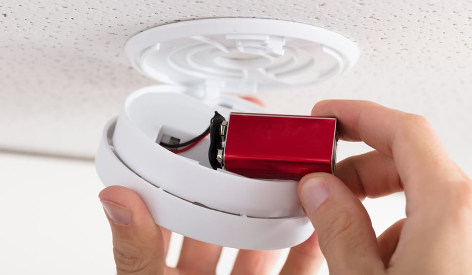close up of a hand changing a battery in a smoke detector