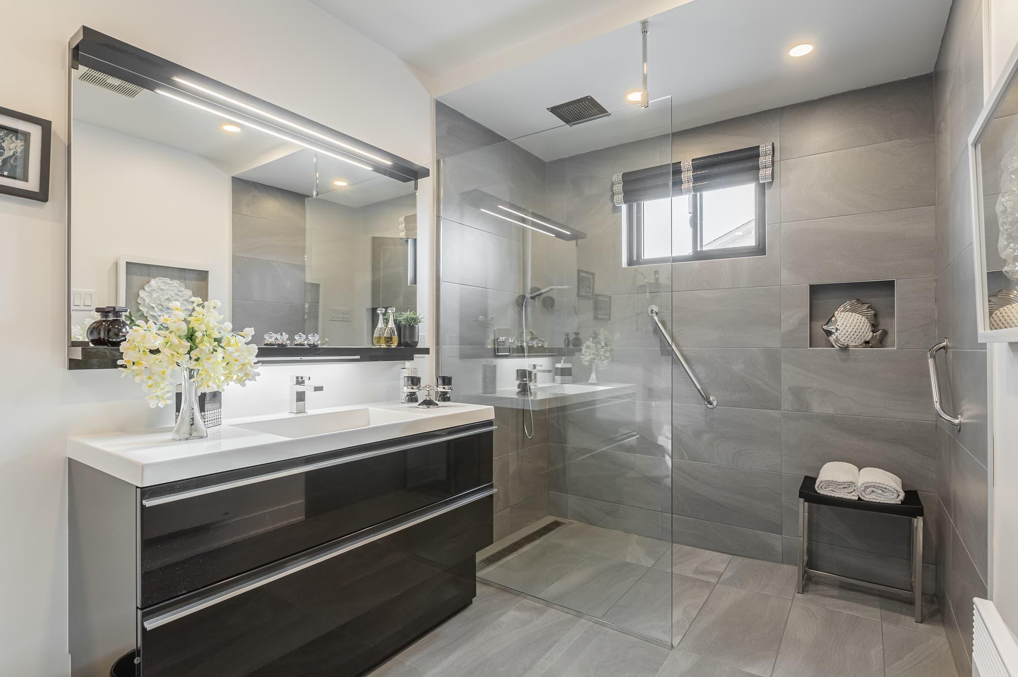 grey bathroom with walk-in shower and black vanity