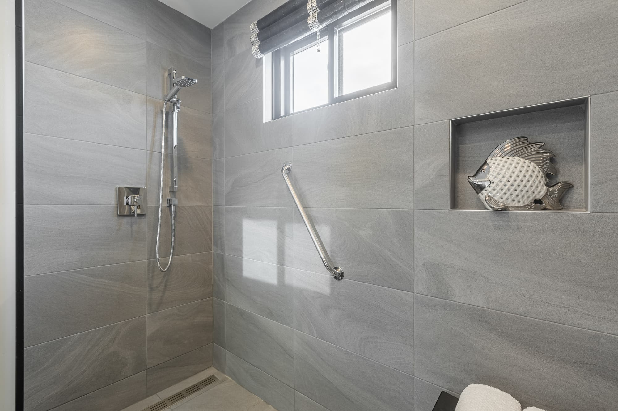 walk-in shower with grey tiles and handrails