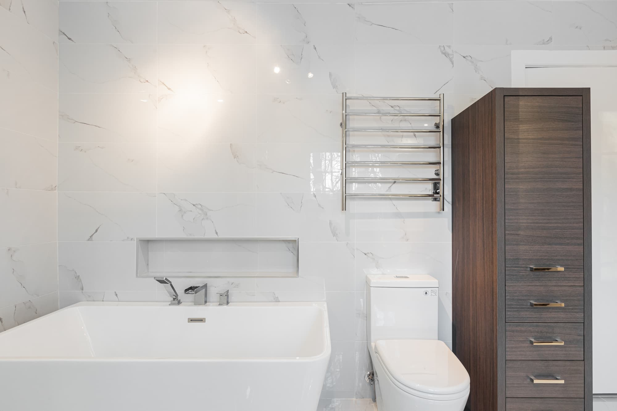 bathroom with free-standing soaker tub with marble tile walls