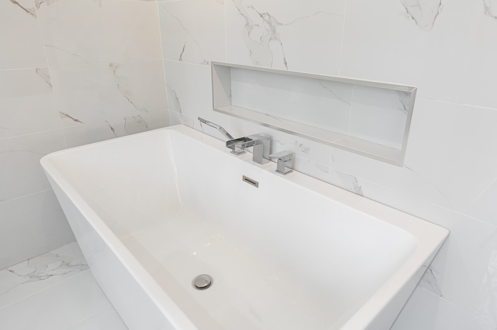 large soaker tub with marble tile walls