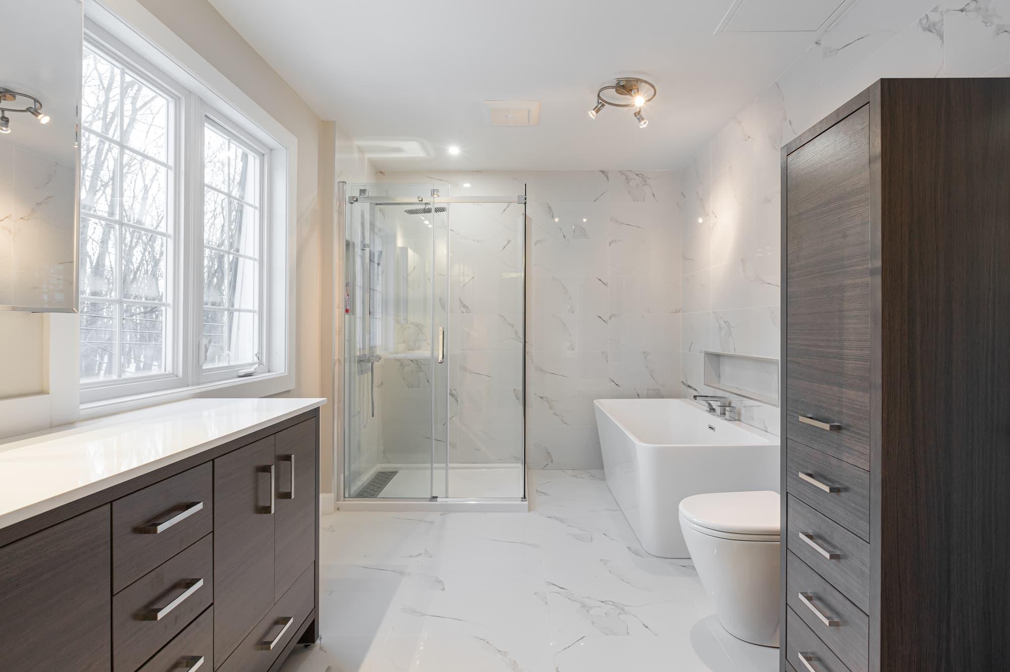 salle de bain moderne rénovée avec bain autoportant rectangulaire et vanité sur mesure