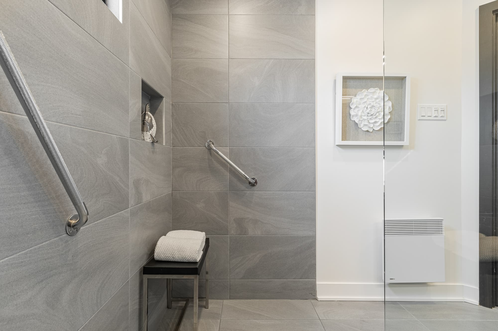 walk-in shower with handrails and grey tiles